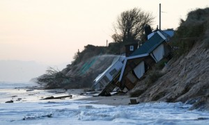 Collapsed houses lie on the beach after a storm surge in Hemsby, eastern England, 6 December 2013. Parts of England's east coast, from Yorkshire to Essex are vulnerable to stronger storms and rising sea levels due to climate change.  Credit: Darren Staples/Reuters