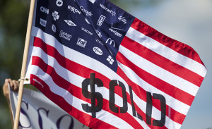 A demonstrator displays a flag decrying corporate spending in US political elections in front of the Waukesha Convention Center on July, 13, 2015, in Waukesha, Wisconsin. Credit: Juli Hansen / Shutterstock.com